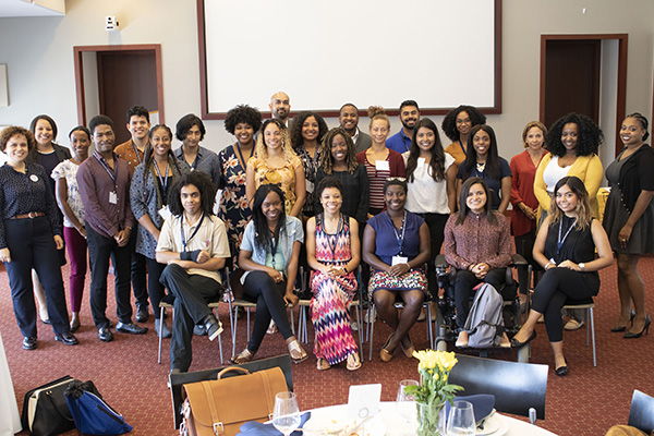 A large, diverse group of 30 students, faculty and staff pose and smile at a reception.